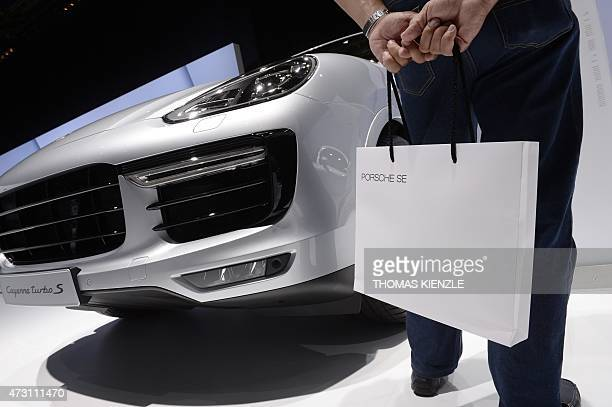 A man holds a bag with the logo of Porsche SE as he stands next to a Porsche Cayenne turbo S car in the showroom during the shareholders' annual...