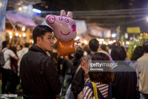 A man holds a balloon in the shape of Peppa Pig at the Lunar New Year fair at Victoria Park at night in Hong Kong China in Sunday Feb 3 2019 Hong...