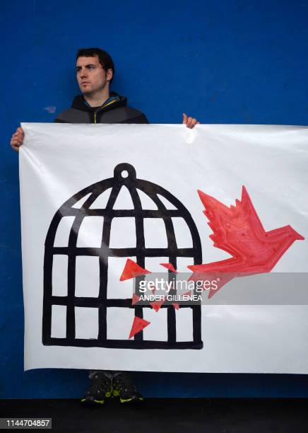A man holds a banner depecting a dove flying from a cage during demonstration in the village of Miraballes on May 18 2019 calling for the release of...
