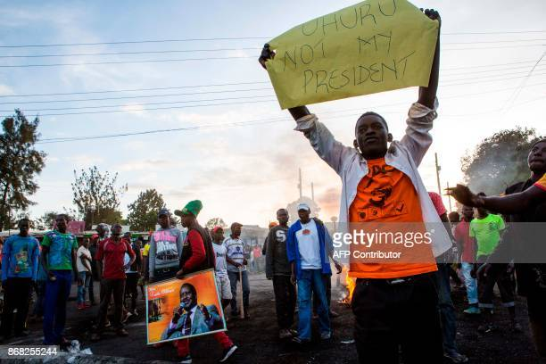 A man holds a banner during a demonstration by supporters of Kenya's opposition National Super Alliance following the announcement of results of a...
