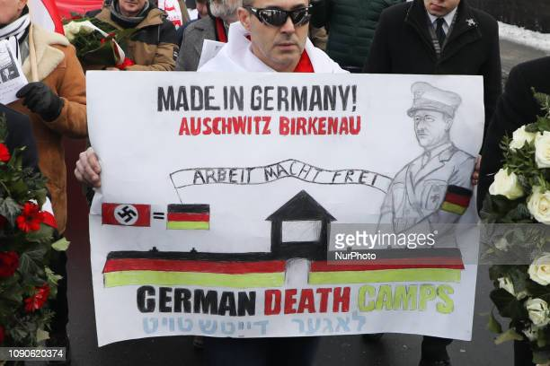 A man holds a banner 'German Death Camps' during a march organized by farright activists and nationalistic groups on the day of the 74th anniversary...