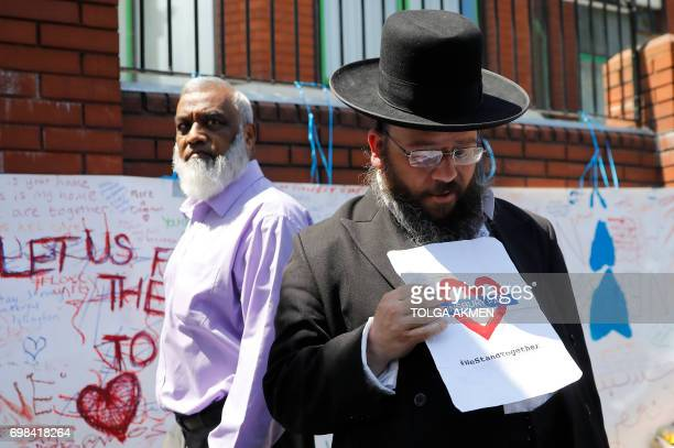 A man holds a banner reading 'Finsbury Park We Stand Together' as he stands outside of Finsbury Park Mosque in the Finsbury Park area of north London...