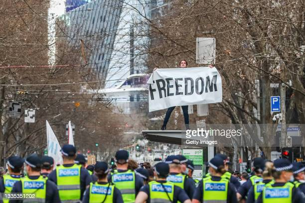 """Man holds a banner reading """"Freedom"""" atop a tram stop during an anti-lockdown protest on August 21, 2021 in Melbourne, Australia. Anti-lockdown..."""