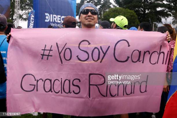 A man holds a banner reading #IAmCarchi Thank You Richard as people celebrate in the streets of Quito after Ecuadorean cyclist Richard Carapaz from...
