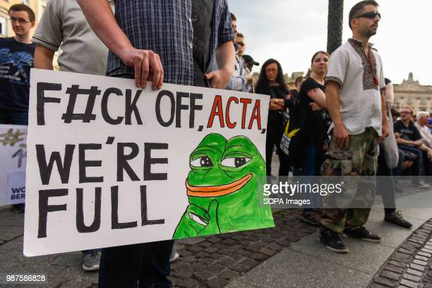 A man holds a banner saying 'F#uck off ACTA we are full ' during a protest against the implementation of ACTA 2 in European Union On June 20th The...