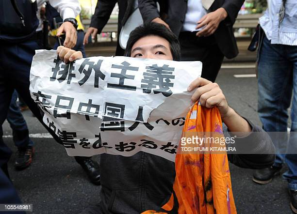 A man holds a banner saying 'Stop fuelling harassment towards Chinese residents in Japan' surrounded by police officers after he sat in front of an...