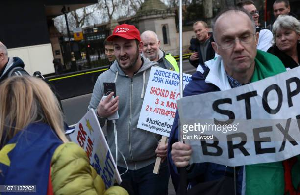A man holds a banner supporting 'justice for josh harry and George' among anti Brexit supporters outside the Houses of Parliament on December 10 2018...
