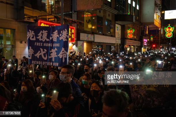 """Man holds a banner that reads in Chinese """"liberate Hong Kong revolution of our times"""" as people raise their phone lights during a pro-democracy rally..."""