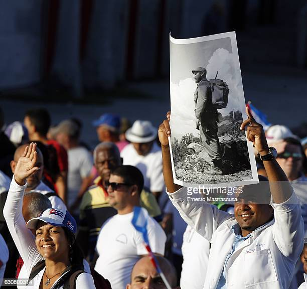 A man holds a banner with the image of former Cuban leader Fidel Castro during a parade to celebrate the 58th anniversary of the Cuban Revolution on...