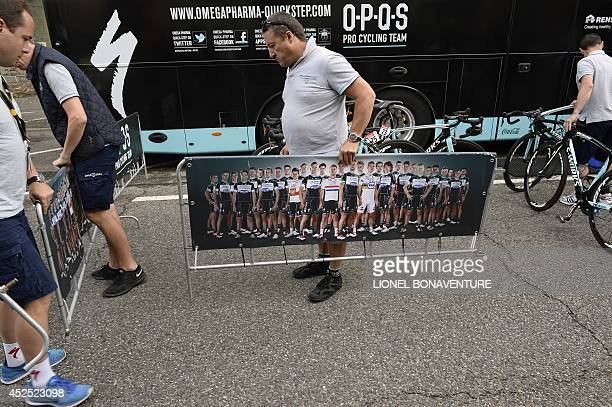 Man holds a barrier bearing a picture of the riders of the Belgium's Omega Pharma - Quick Step cycling team, at the departure village in Carcassonne,...