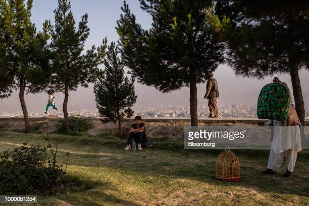 A man holds a bird cage as people walk through a park at the top of Bibi Mahru Hill in Kabul Afghanistan on Sunday July 15 2018 US President Donald...