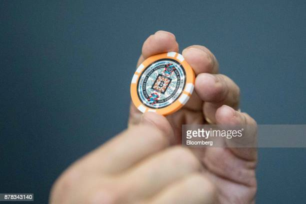 A man holds a bitcoin token inside the offices of La Maison du Bitcoin bank in Paris France on Thursday Nov 23 2017 Zimbabwe where the price of...