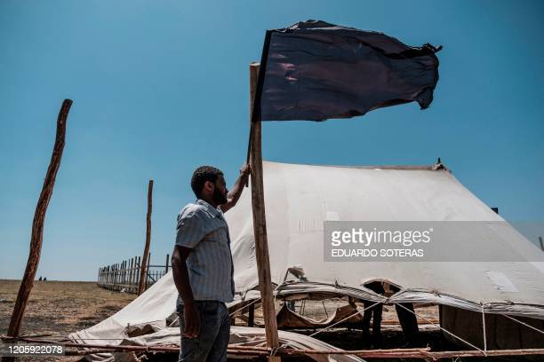 A man holds a black flag during a memorial ceremony at the crash site of the Ethiopian Airlines Flight 302 airplane accident in Tulu Fara Ethiopia on...