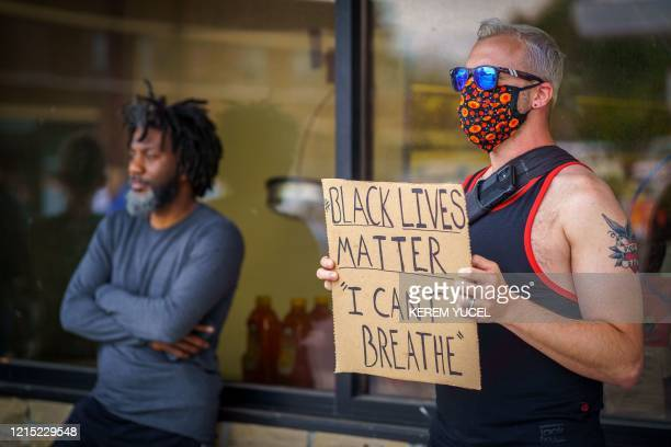 A man holds a 'Black Lives Matter I can't breathe placard while protesting near where a Minneapolis Police Department officer allegedly killed George...