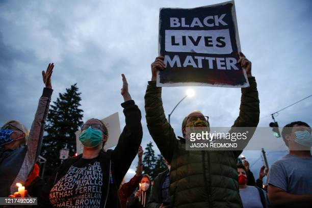 A man holds a black lives matter sign as family friends and community members attend a vigil at the intersection where Manuel Ellis a 33yearold black...