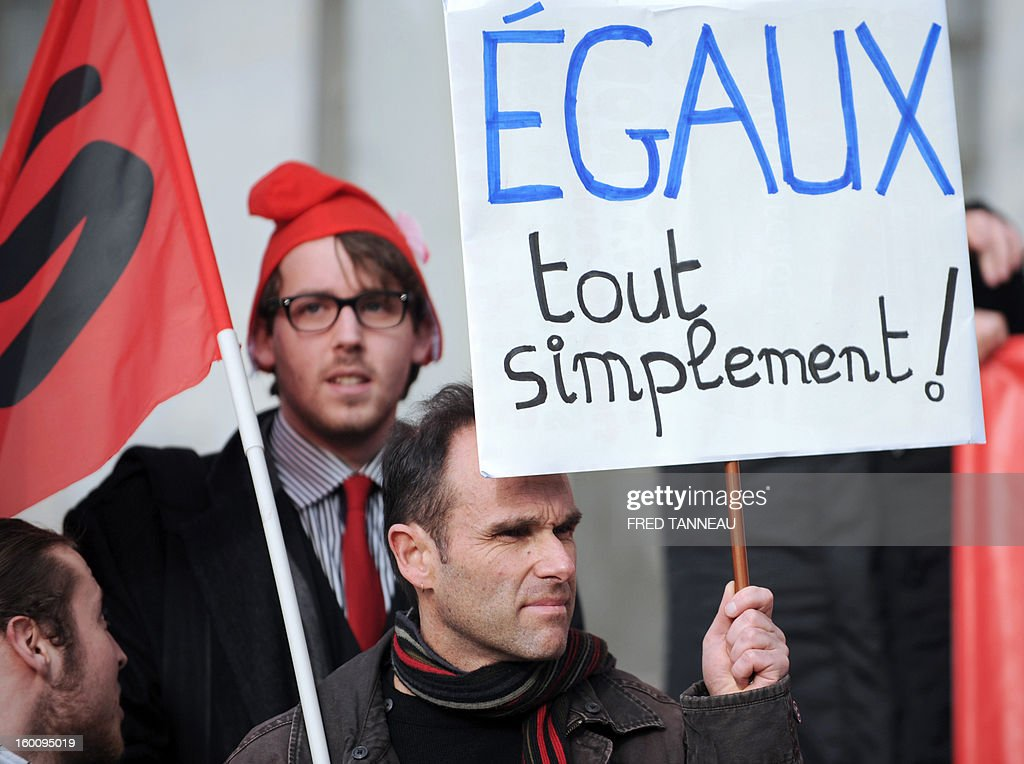 A man holds a board which reads 'Simply equal' as he demonstrates among some four hundred on January 26, 2013 in Brest, western France, during a meeting to support gay marriage and adoption. French government plans to put the proposed legislation to parliament on January 29.