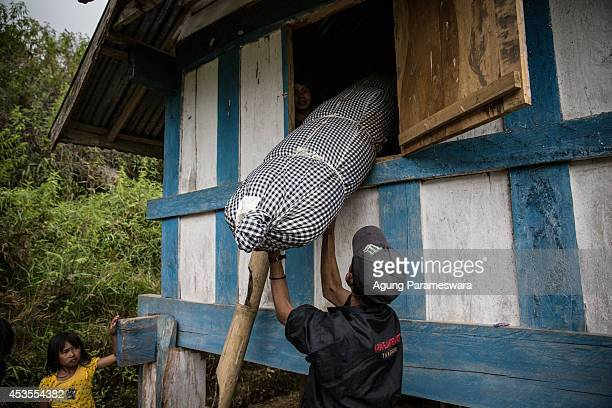 A man holds a body of deceased to put out from a Patane during Manene ritual on August 13 2014 in Toraja South Sulawesi Indonesia The Manene ritual...