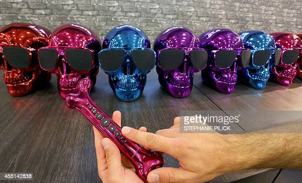 A man holds a boneshaped remote control in front of loudspeakers designed as skulls at the both of the Jarre company at the consumer electronics...