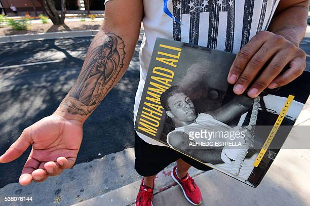 A man holds a book of boxing legend Muhammad Ali outside the Scottsdale Healtcare Hospital where Ali died in Scottsdale Arizona on June 4 2016 Ali an...