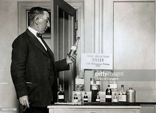 A man holds a bottle from a display of alcohol used in a prohibition case A sign above the bottles reads 'The decoctions killed 215 Chicagoans During...