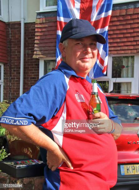 Man holds a bottle of beer with a large Union Jack in the background celebrating during the commemoration. The VE Day 75th anniversary, when Victory...