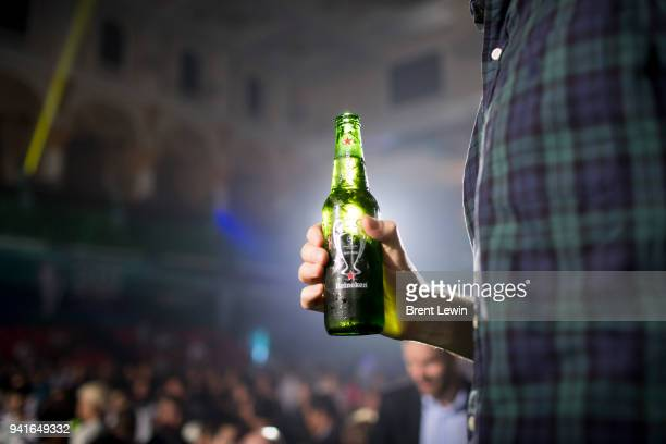 A man holds a bottle of Heineken beer during the UEFA Champions League Trophy Tour presented by Heineken on April 3 2017 in Phnom Penh Cambodia