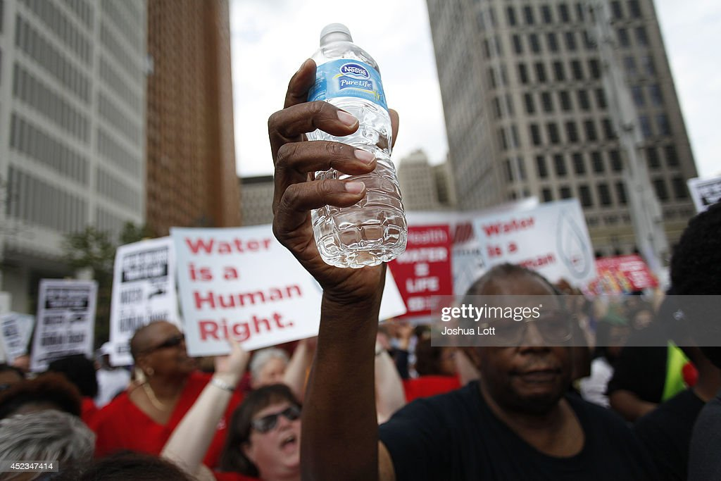 A man holds a bottle of water as he joins other demonstrators protesting against the Detroit Water and Sewer Department July 18, 2014 in Detroit, Michigan. The Detroit Water and Sewer Department have disconnected water to thousands of Detroit residents who are delinquent with their bills.