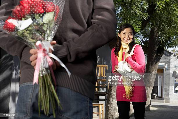 A man holds a bouquet of roses behind his back.