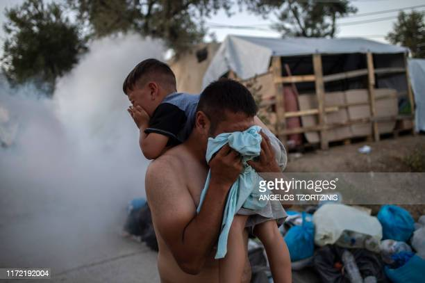 A man holds a boy and protects himself from tear gas during clashes with police outside the refugee camp of Moria on the Greek island of Lesbos on...