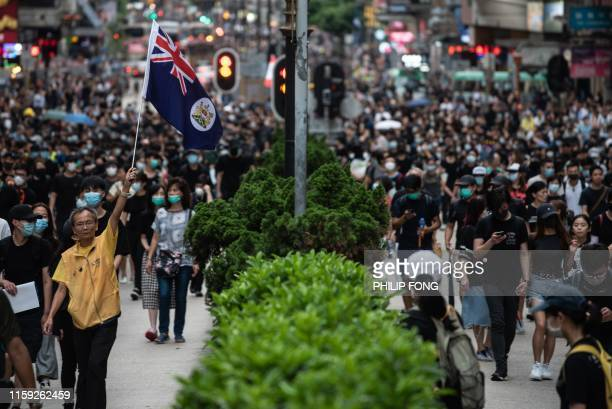 A man holds a British colonial flag duing a rally along Nathan Road in Hong Kong on August 3 in the latest opposition to a planned extradition law...