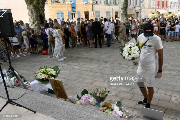 Man holds a bunch of flowers during a ceremony in Le Plan-de-la-Tour, southeastern France on July 21 to pay a tribute to Doriane, a young woman who...