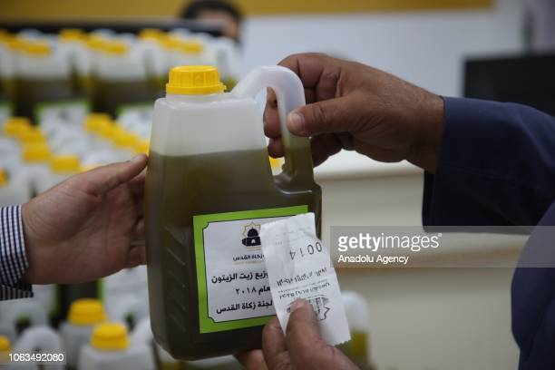 A man holds a can of olive oil at a facility after being picked from an olive tree to distribute to the ones in need at the Masjid alAqsa Compound in...