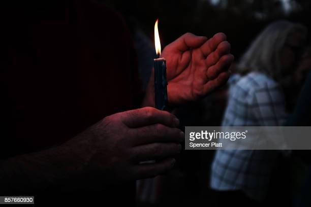 A man holds a candle as dozens of people attend a vigil remembering the 58 people killed in Sunday's shooting in Las Vegas and calling for action...