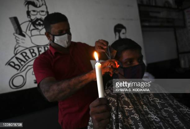 TOPSHOT A man holds a candle as he gets a hair cut in Colombo on August 17 during a lengthy electricity outage affecting the entire country of more...