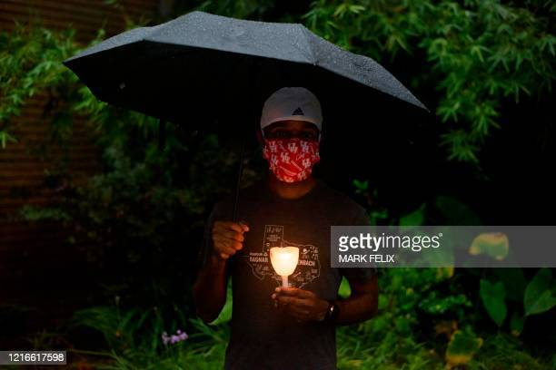 A man holds a candle as members of the community gathered to mourn the death of George Floyd during a candle light vigil at Resurrection Metropolitan...