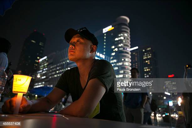 A man holds a candle as protesters continue their fight at the Sewol ferry protest camp September 16 2014 in Seoul South Korea Korean protesters are...