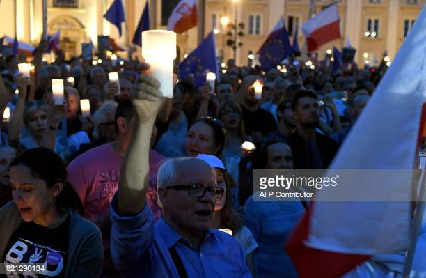 Man holds a candle as protesters take part in a demonstration in front of the Polish Supreme Court on July 23 in Warsaw to protest against the new...