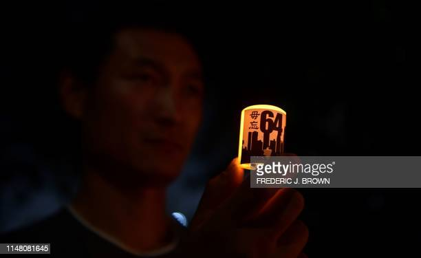"Man holds a candle with words and numbers ""never forget 64"" during a candlelight vigil in front of the Chinese Consulate in Los Angeles, California..."