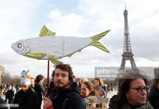 A man holds a cardboard depicting a fish during a demonstration of the Sardine Movement formed to oppose the farright League party in front of the...