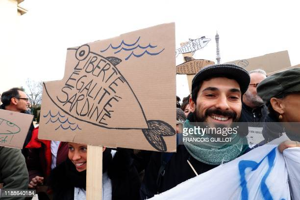 A man holds a cardboard depicting a fish reading Freedom equality Sardinies during a demonstration of the Sardine Movement formed to oppose the...