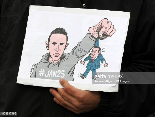 Man holds a cartoon showing President Obama with the Egyptian president Hosni Mubarak in his hand during the Scottish Palestine Solidarity Campaign...