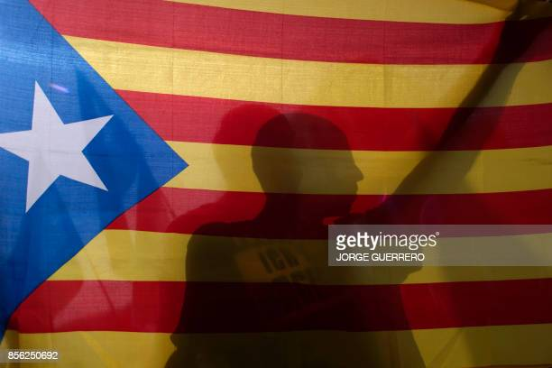 A man holds a Catalan proindependence 'Estelada' flag during a demonstration in support of the referendum in Catalonia on October 01 in Granada