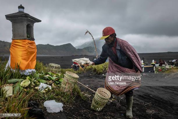Man holds a chicken caught after being thrown as a offering by Tenggerese during the Yadnya Kasada Festival at the crater of Mount Bromo amid the...