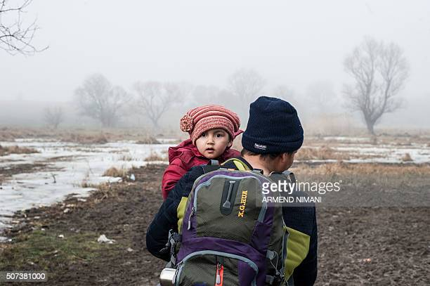A man holds a child as he walks with other migrants and refugees after crossing the Macedonian border into Serbia near the village of Miratovac on...