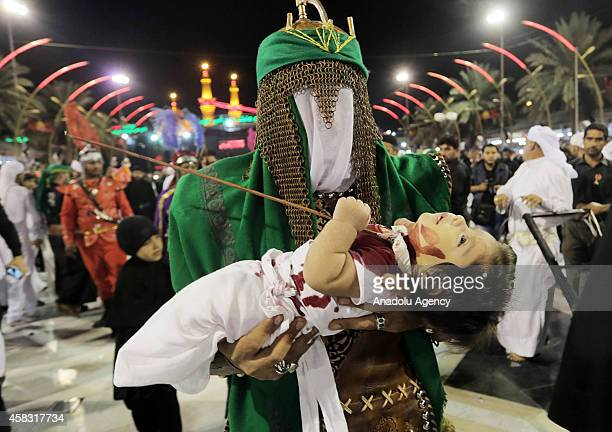 A man holds a child to symbolise martyred Husayn inb Ali's grandson Abdullah in Karbala Iraq on November 3 2014 Shiites attend the commemoration...