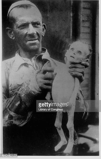 A man holds a child who has starved to death as a result of Hitler's New Order which intended to exterminate whole peoples including the Poles