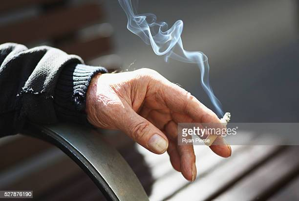 A man holds a cigarette on May 04 2016 in Sydney New South Wales The Australian Government yesterday announced in their budget four annual 125 per...