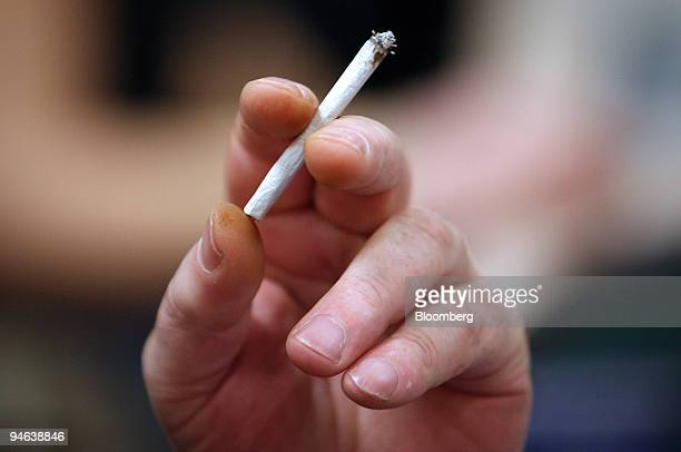 A man holds a cigarette while playing bingo at Beacon Bingo in Cricklewood Broadway north London on Wednesday December 13 2006 Bingo parlors once the...