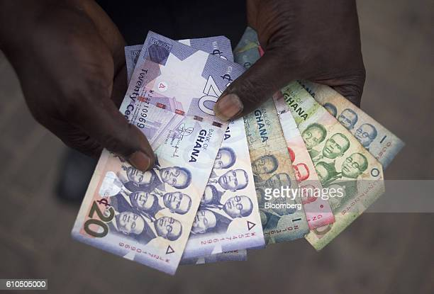 A man holds a collection of Ghana cedi banknotes in Accra Ghana on Tuesday Sept 20 2016 Ghana's central bank expects mergers and acquisitions among...