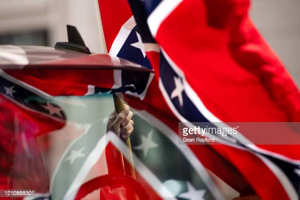 Man holds a Confederate flag while participating in a protest against government closures of non-essential businesses due to the coronavirus on April...